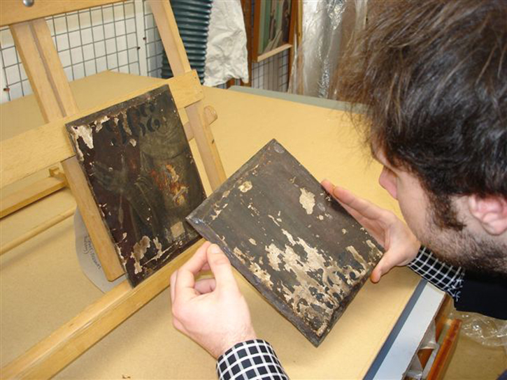 A researcher examines a painting