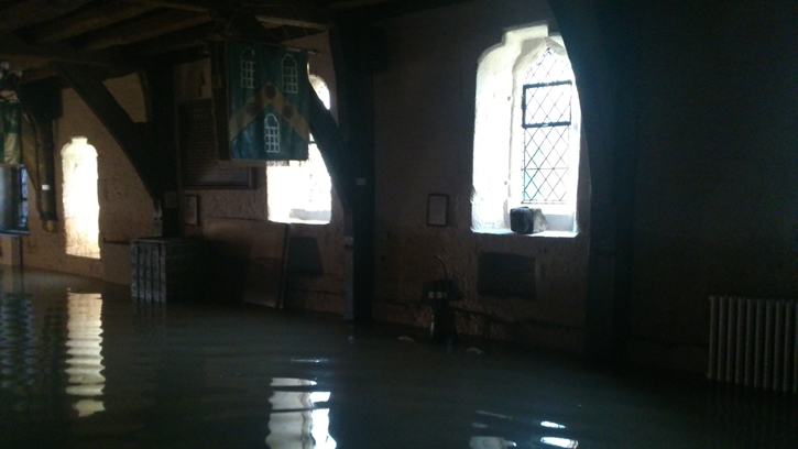 The muddy walls and flood water in the Undercroft