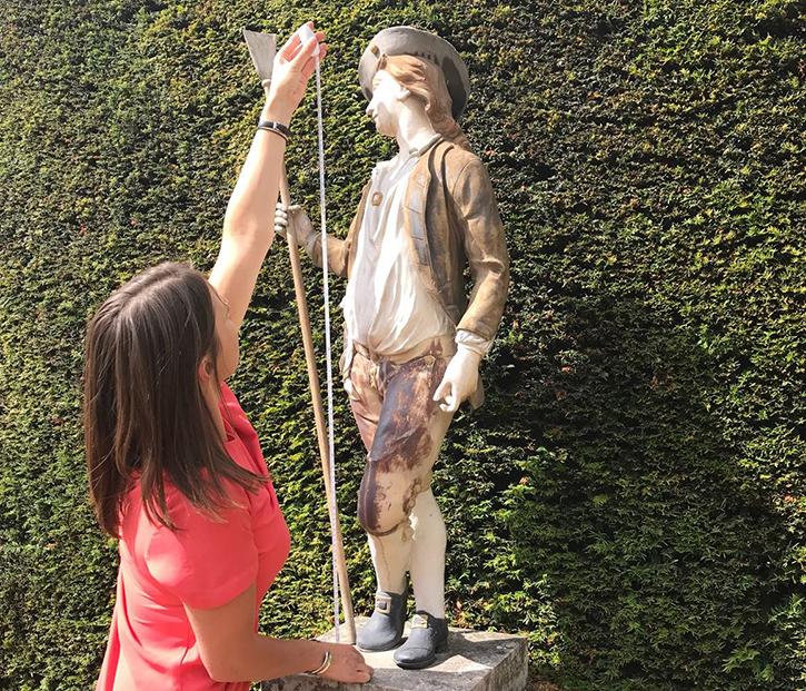Coordinator Elizabeth Heath measures a sculpture during a photography session