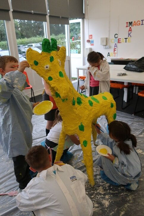 Children paint their giraffe sculpture
