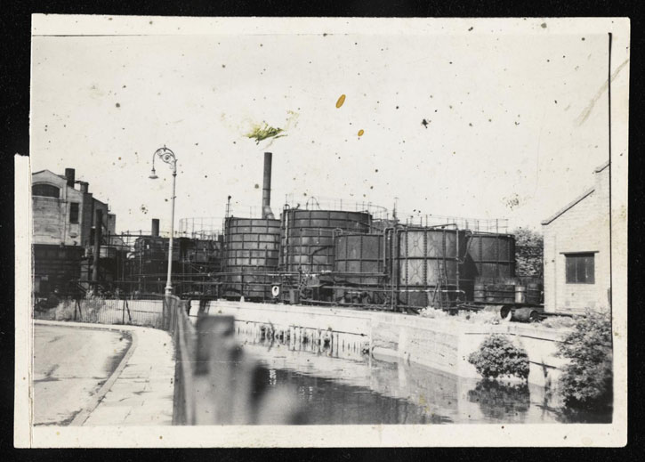 Black-and-white photograph of a canal and gas works