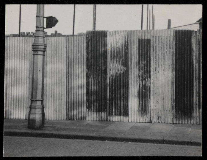 Black-and-white photograph of corrugated iron hoardings