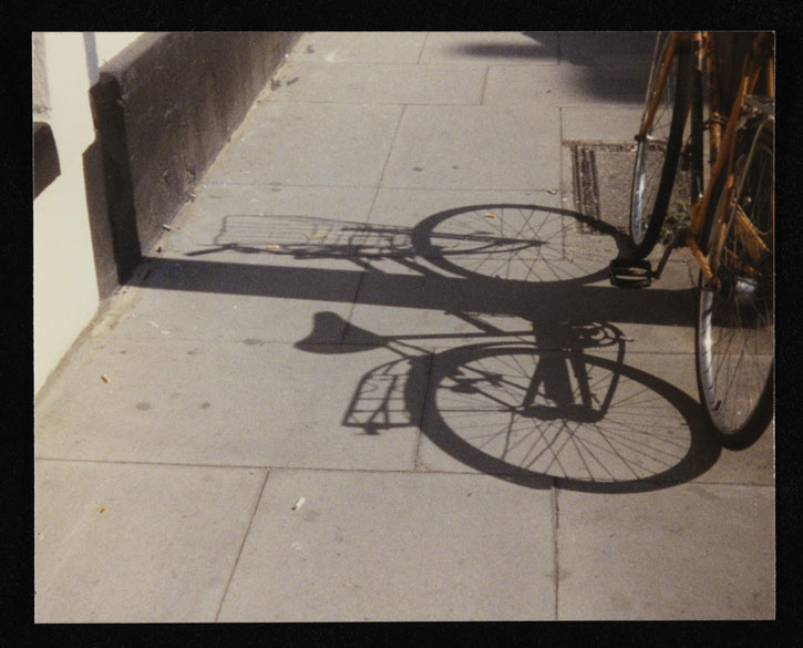 Colour photograph of the shadow of a bicycle on the pavement