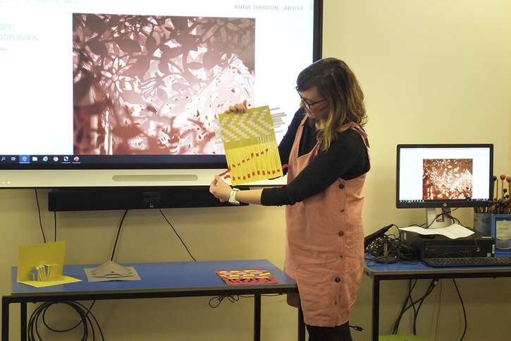 Anna Shirron showing students different ways of manipulating paper to create different effects