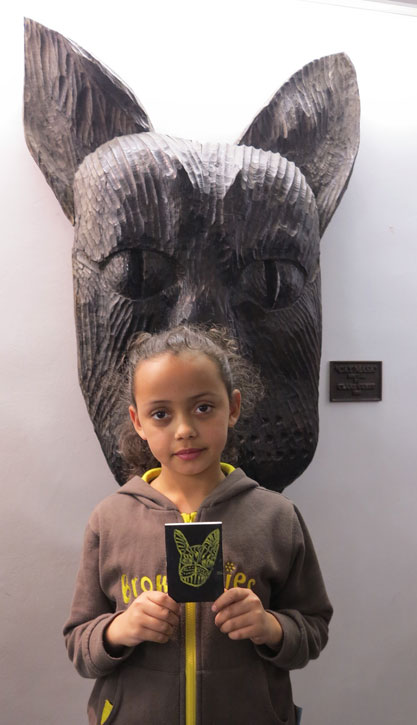A Harlow Brownie with her drawing of the 'Cat Mask (1)' sculpture behind her