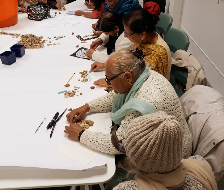 At Leeds Art Gallery a group of visitors create sculpture from stones during a VocalEyes workshop