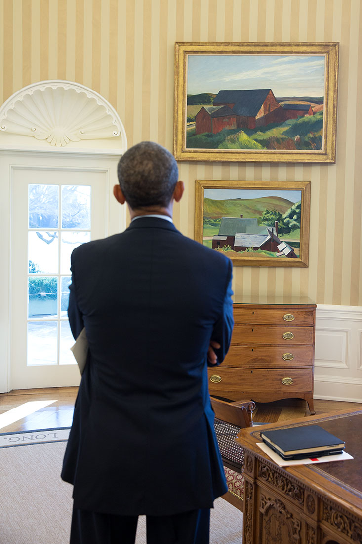 President Barack Obama looks at the Edward Hopper paintings displayed in the Oval Office