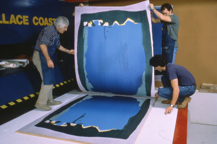 Kenneth Tyler, Robert Myer and Tom Strianese pulling proof impression from Helen Frankenthaler's 'Freefall' assembled woodblocks on hydraulic platen press in the workshop, Tyler Graphics Ltd., Mount Kisco, New York, 1992