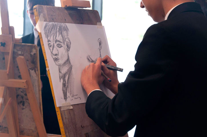 A student tries out drawing with both hands
