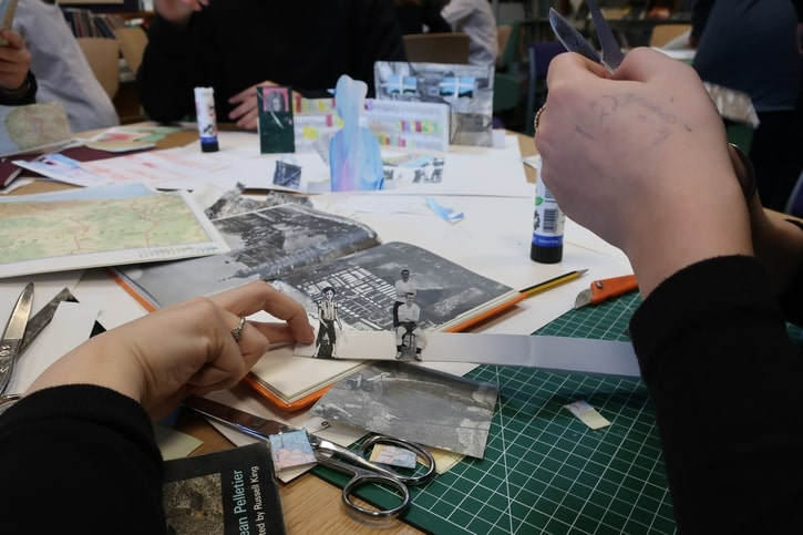 Students glue cut-out images to one of their pop-up layers