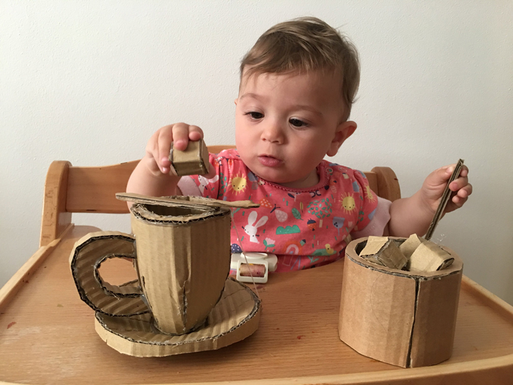 The artist's daughter enjoys putting sugar cubes in her make-believe cup of tea!