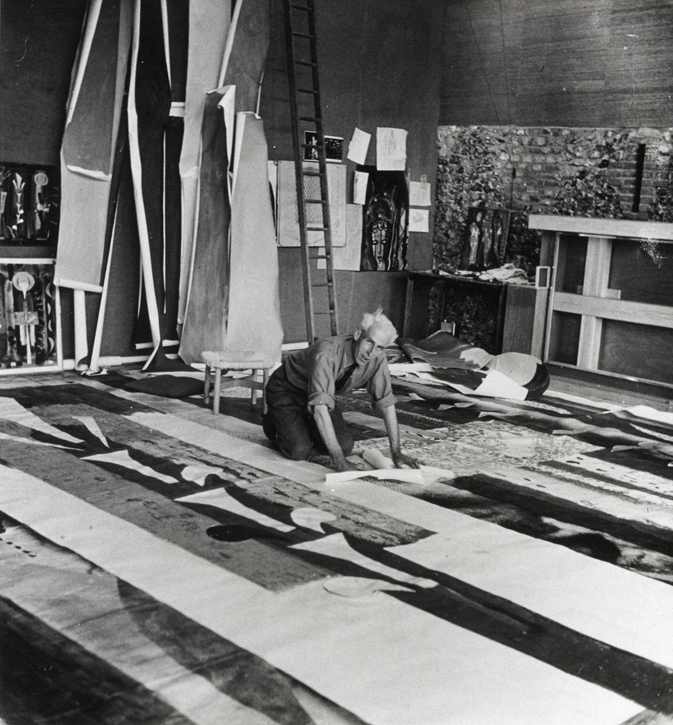John Piper in his studio at Fawley Bottom, cutting the design for the stained glass window