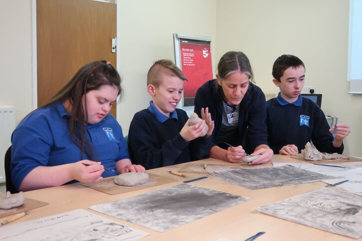 Pupils work with sculptor Shona Kinloch to create a relief in clay
