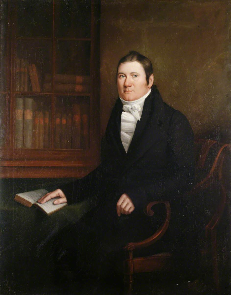Portrait of a Man Sitting at a Table with an Open Book