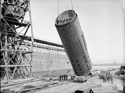 Number 3 funnel being hoisted to vertical position on dockside by floating crane