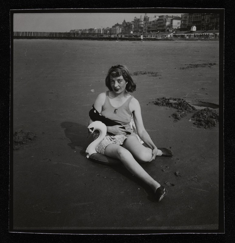 Photograph of Eileen Agar sitting on a beach with a plastic swan