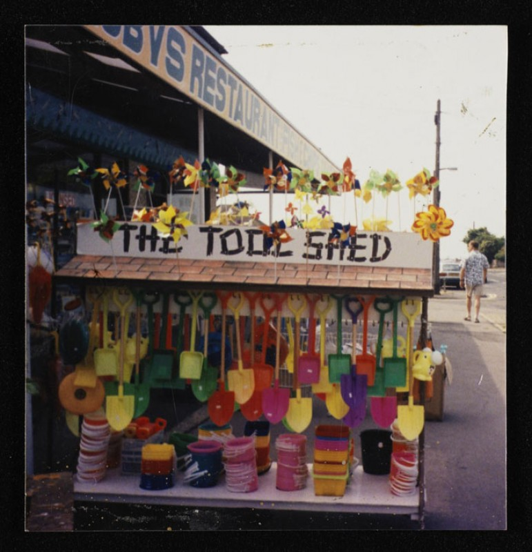 Colour photograph of a stall called 'The Tool Shed' selling plastic buckets and spades