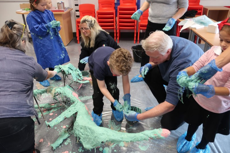 Children apply plaster to an armature at Newhall Academy