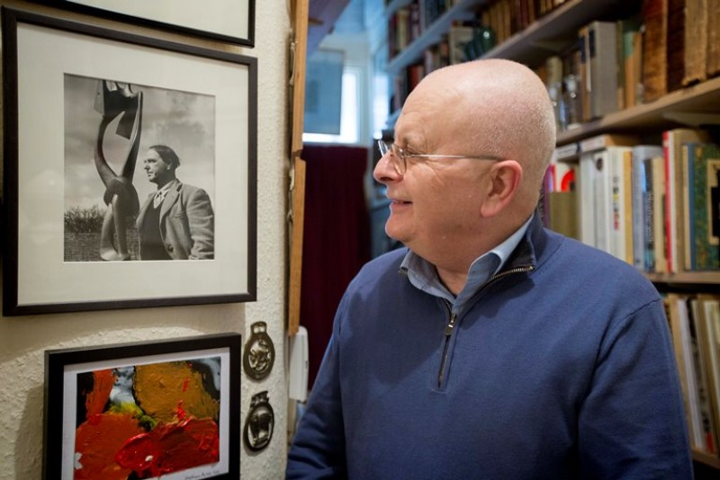 Tim Sayer in his London home, looking at a print of artist Henry Moore