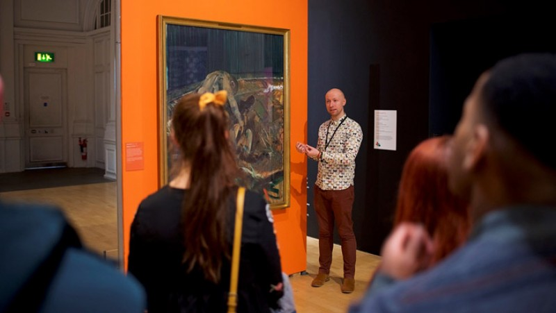 Jon Sleigh giving a talk in front of Francis Bacon's 'Figures in a Landscape'
