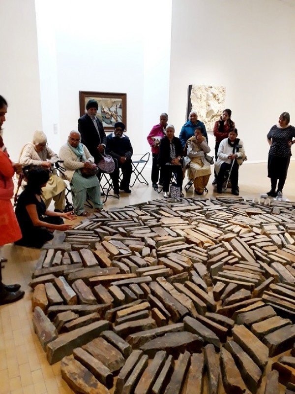 A group explores a Richard Long artwork at Leeds Art Gallery during a VocalEyes Art UK workshop
