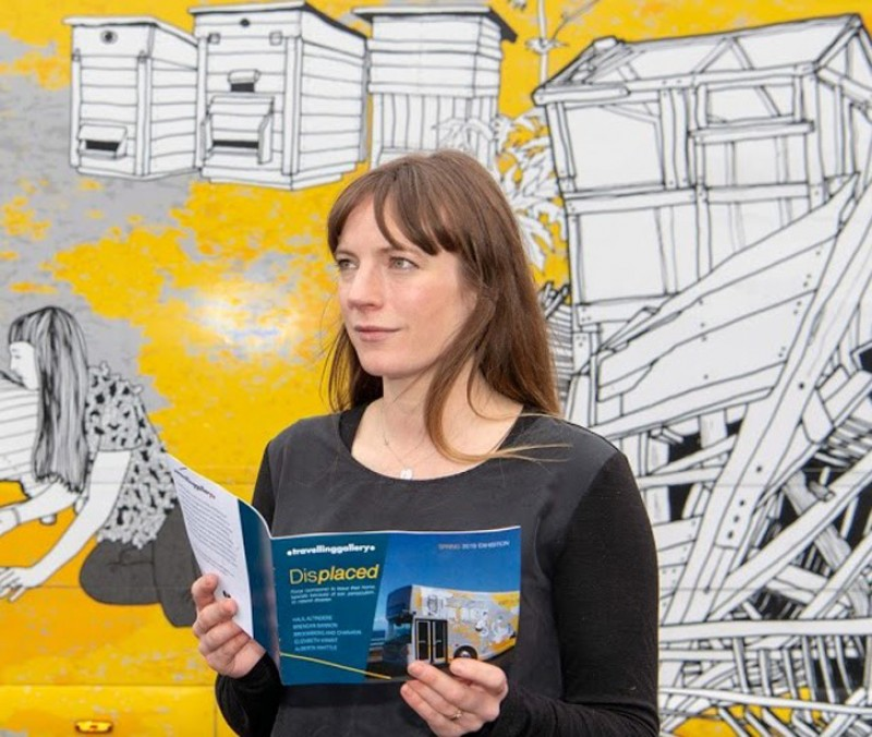 Curator Claire Craig in front of the Travelling Gallery ahead of the exhibition 'Displaced'