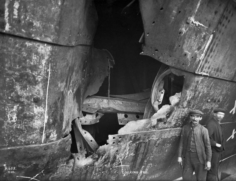 HMS 'Hawke' collision damage – middle hole looking forward, with two figures
