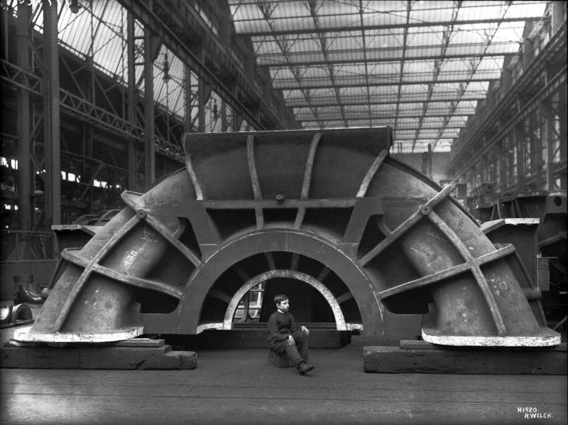 Turbine cover in erecting shop, with apprentice seated to give scale