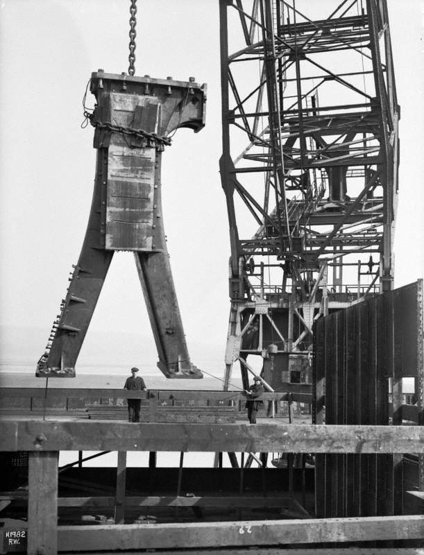 Pillar of engine being lifted from dockside by floating crane