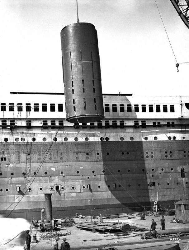 Number 3 funnel being lifted onto ship by floating crane, seen from dockside