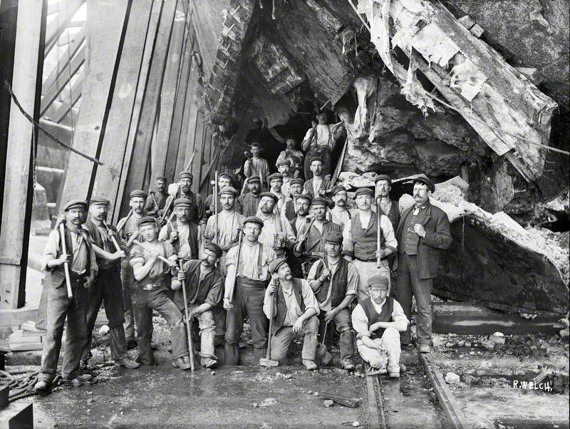 The 'Black Squad' posed beneath the damaged section of hull